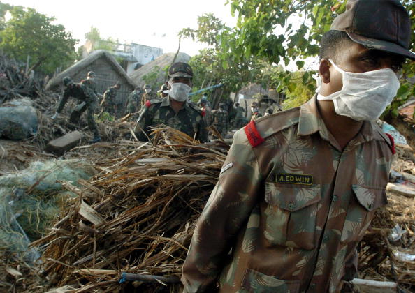 Officers of the Indian army carry debris