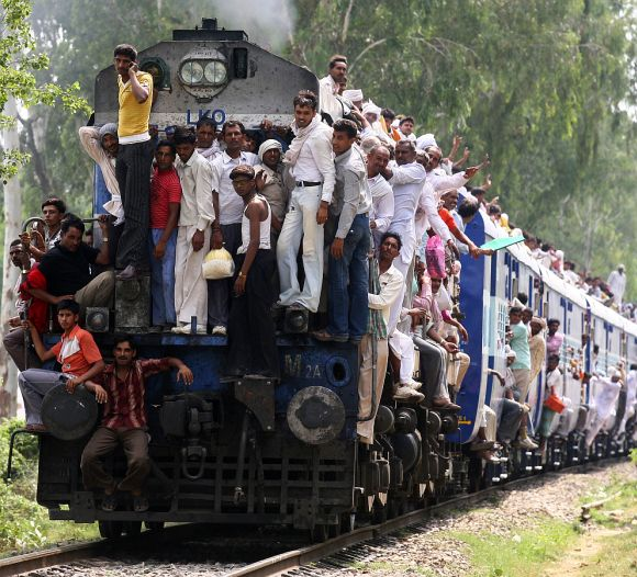 Hindu devotees travel in overcrowded passenger train after taking holy dip and offering prayers in waters of Brahma Sarovar