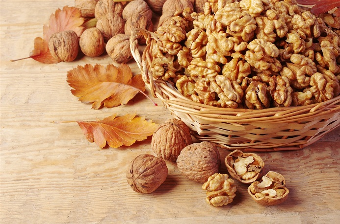 Walnut-kernels-in-basket-and-whole-walnuts-on-rustic-old-wood