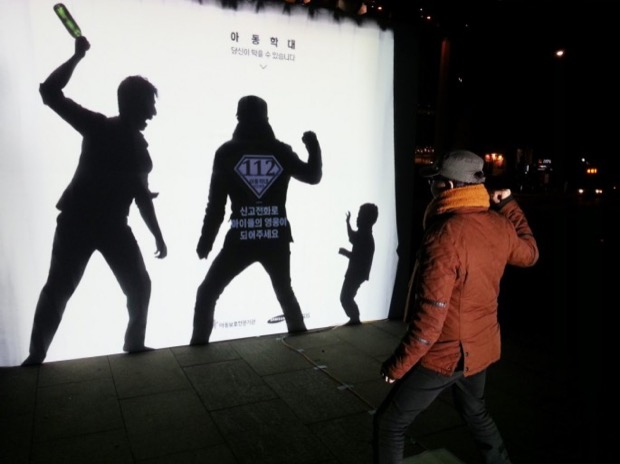 man standing in front of anti childabuse ad
